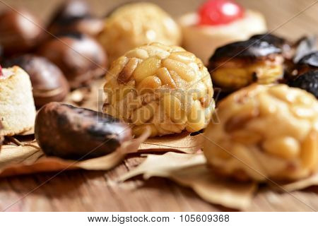 closeup of some roasted chestnuts and some panellets, typical snack in All Saints Day in Catalonia, Spain, and dry leaves on a rustic wooden surface