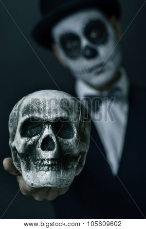 scary portrait of a young man with mexican calaveras makeup, wearing top hat and bow tie and holding a scary skull in front of him