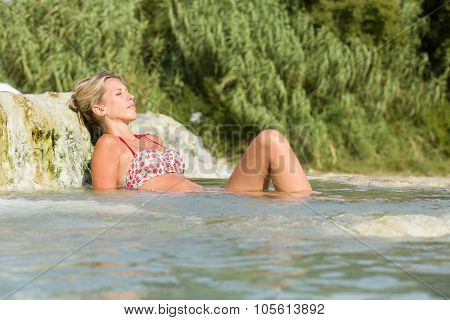 Natural pool, woman lays in warm water outdoor