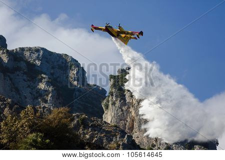 Yellow fire fighter aircraft drops all the water