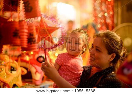 HANOI, VIETNAM, SEPT 5: A man with his child in a shop for Mid-Autumn festival. Parents often buy lanterns for their children in this occasion.
