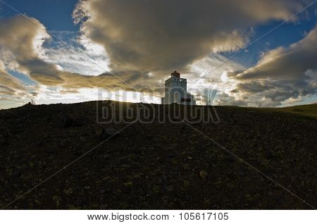Lighthouse at Dyrholaey rock at sunset with dramatic sky
