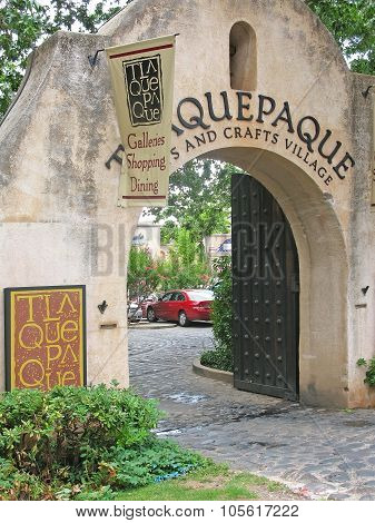 Tlaquepaque entrance portal with signs and flags