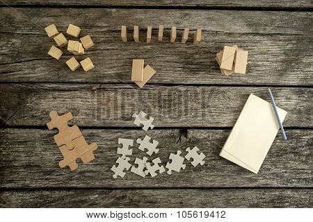 Blank Notepad, Pencil And Piles Of Puzzle Pieces, Wooden Blocks And Pegs Lying On Desk