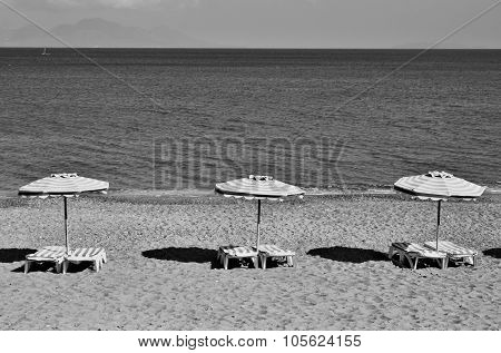 Greece. Kos. Kefalos Beach. Chairs And Umbrellas On The Beach. In Black And White