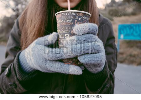 Young Woman In Knitted Gloves Drinking Coffee From Disposable Cup Through A Straw During Autumn Walk