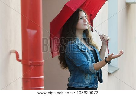 Urban portrait of pedestrian girl carrying plain red umbrella standing with palm up outstretched arm