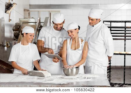 Male and female Baker's using digital tablet together at table in bakery