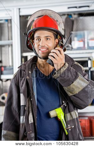 Young male firefighter looking away while using walkie talkie at fire station