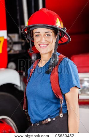 Portrait of smiling firewoman wearing red helmet against firetruck at station