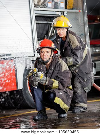 Confident male and female firefighters spraying water during practice at fire station