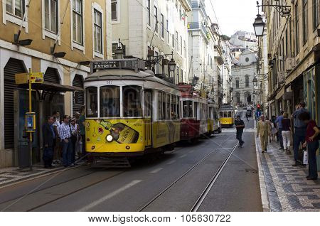 Rua Conceicao Street In Lisbon With A Series Of Trams