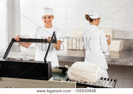 Portrait of confident female baker using vacuum seal machine while coworker working in bakery