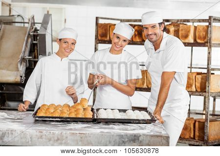 Portrait of confident male and female Baker's standing at table in bakery