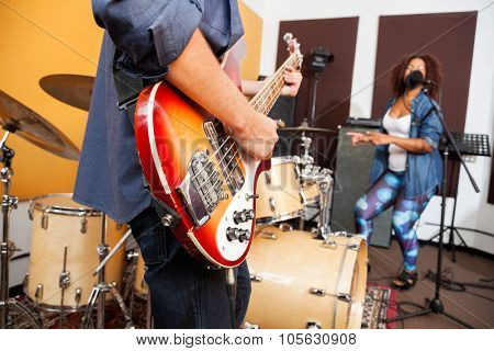Midsection of man playing guitar while woman singing and dancing in background at recording studio