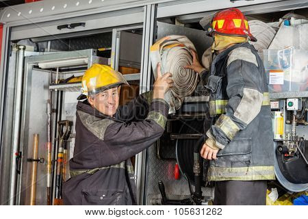 Portrait of smiling male firefighter assisting colleague in removing hose from truck in fire station