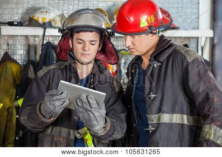 Male firefighters using digital tablet while standing at fire station