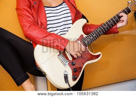 Midsection of young female performer playing guitar in recording studio