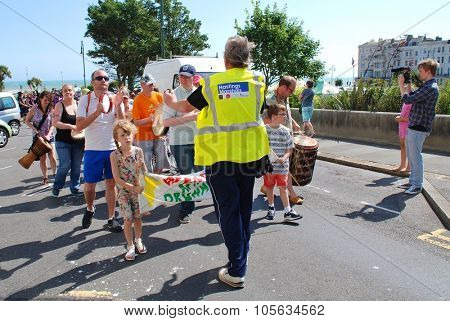 ST.LEONARDS-ON-SEA, ENGLAND - JULY 11, 2015: A marshal guides people taking part in the parade at the annual St.Leonards Festival in Warrior Square.The free entertainment event was first held in 2006.