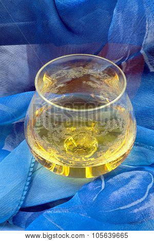 Glass Of Cognac Wrapped In Blue Cloth