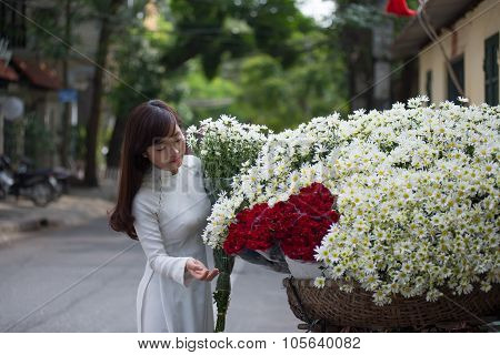 Vietnamese girl in traditional dress buying white daisy flower on street in Hanoi