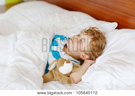 Little Blond Child Sleeping In His Bed With Toy.