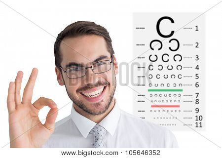 Happy businessman making okay gesture against eye test