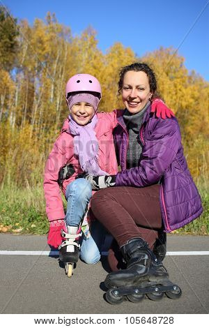 Happy mother with daughter in a protective helmet on roller skates in the autumn park