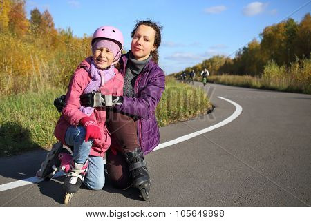 Mother with her daughter in a protective helmet on roller skates in the autumn park