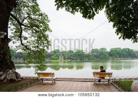 People sit near Hoan Kiem lake (or Sword Lake) in Hanoi, Vietnam
