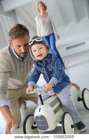 Man helping little boy on a riding toy