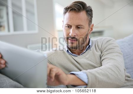 Handsome man at home websurfing on digital tablet