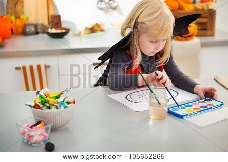Interested Halloween Dressed Girl Drawing Pumpkin Jack-o-lantern