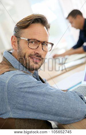 Portrait of trendy man working on laptop computer