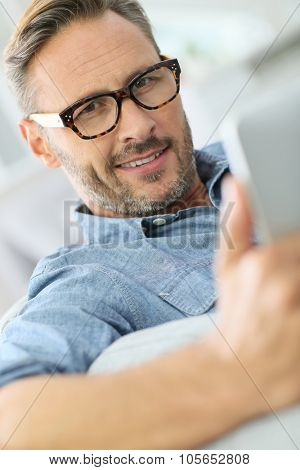 Handsome man with eyeglasses relaxing in sofa with tablet