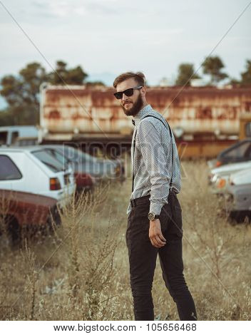 Young Handsome Stylish Man, Wearing Shirt And Bow-tie On The Field Of Old Cars
