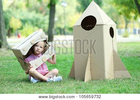 Little girl in carton helmet sitting near carton rocket in  the park