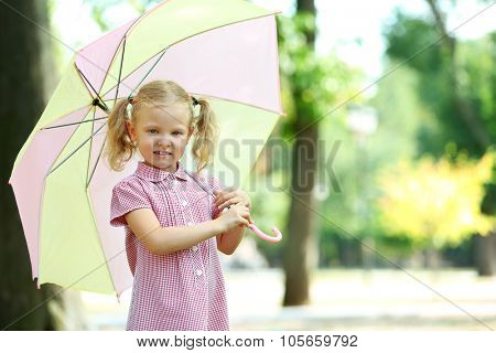 Cute blonde little girl in pink dress under big creamy umbrella at the park