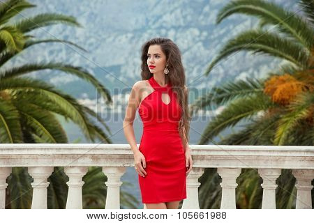 Beautiful Young Sexy Brunette Girl In Red Dress Posing On Balcony View On Palms And Sea Shore Kotor,