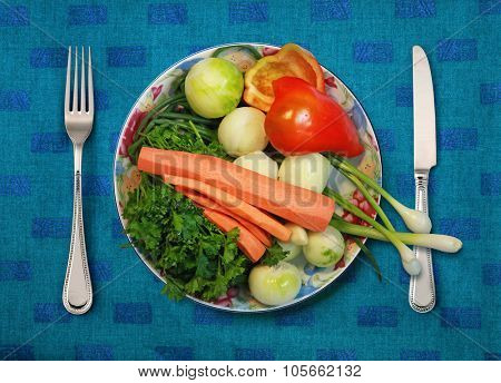 vegetables on white plate, knife and fork