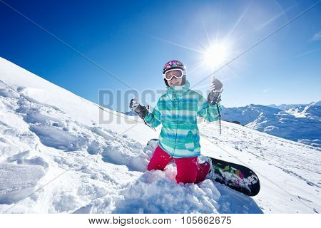 Female snowboarder wearing colorful helmet, blue jacket, gloves and pants sitting on snowy slope and showing thumb up hand gesture with both hands against alpine landscape - winter sports concept