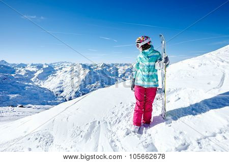 Female snowboarder wearing colorful helmet, blue jacket, grey gloves and pink pants standing with snowboard in one hand and looking at beautiful alpine mountain landscape - winter sports concept
