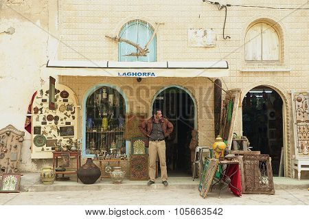 Man stands in at the souvenir shop entrance in El Djem, Tunisia.