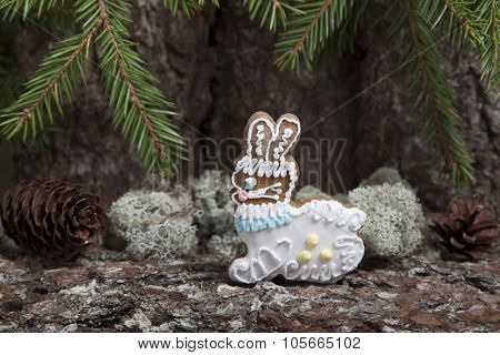 Christmas Gingerbread In The Form Of A Hare On A Background Of An Old Tree Bark With Fir Cones .