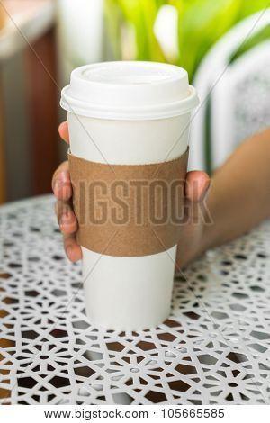 Mock up of disposable cup of coffee in hand