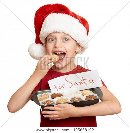 girl in santa hat eat cookies - winter holiday christmas concept