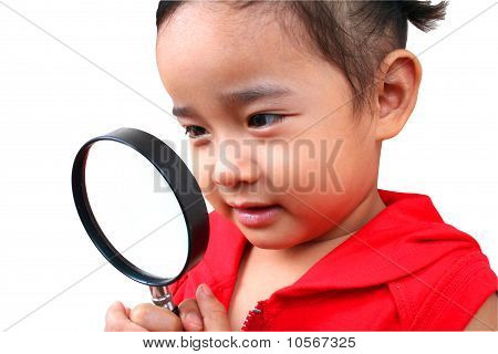 Young girl looking true the magnify glass.
