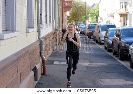 Young Woman Jogging Down An Urban Street