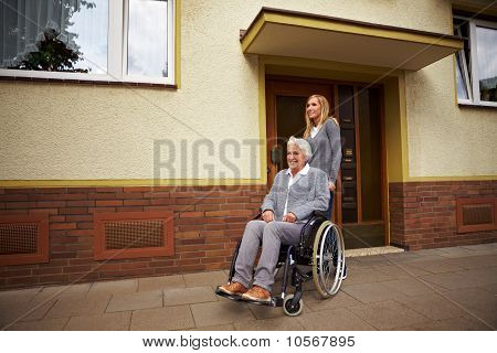 Wheelchair User In Front Of Nursing Home