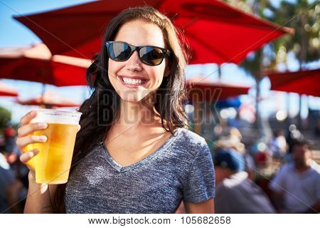 portrait of happy woman holding cup of beer outside on sunny day shot with selective focus